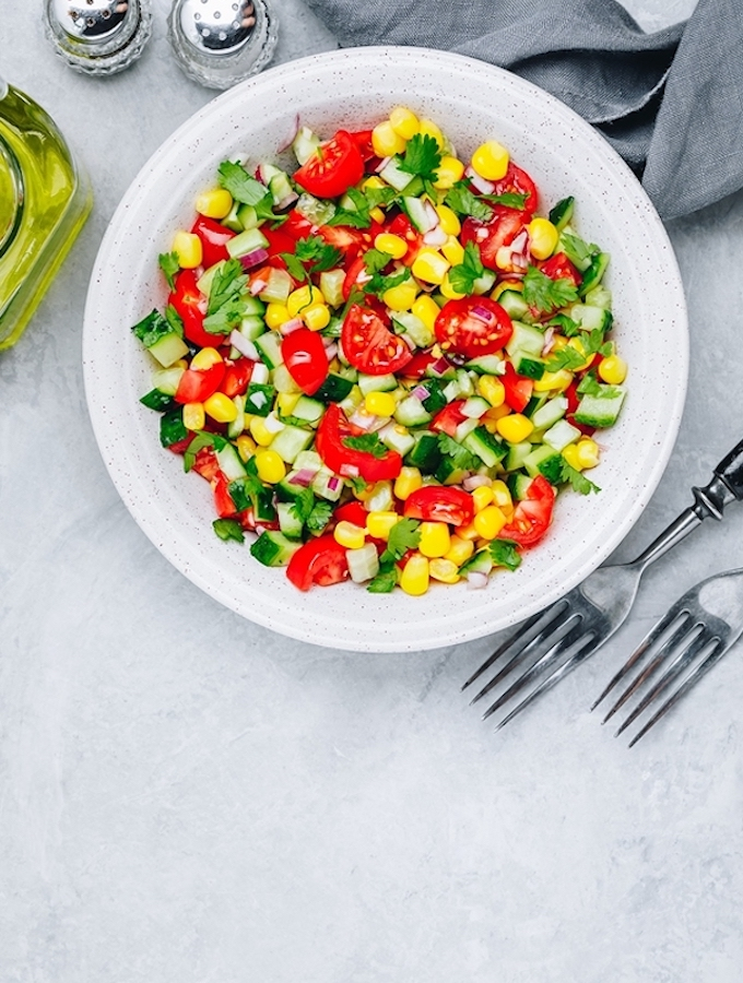 Fresh Summer Corn and tomato saldSalad Bowl With Tomatoes, Cucumbers, Red Onions And Parsley.