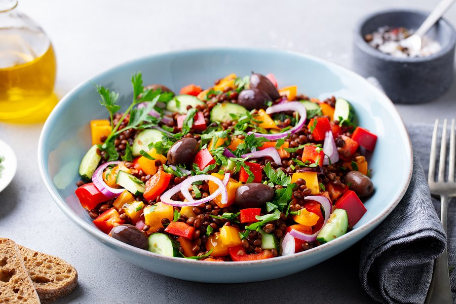 Black lentil salad with olives, peppers, and cucumber
